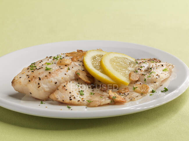 Tilapia fillets with garlic and lemon slices — Stock Photo