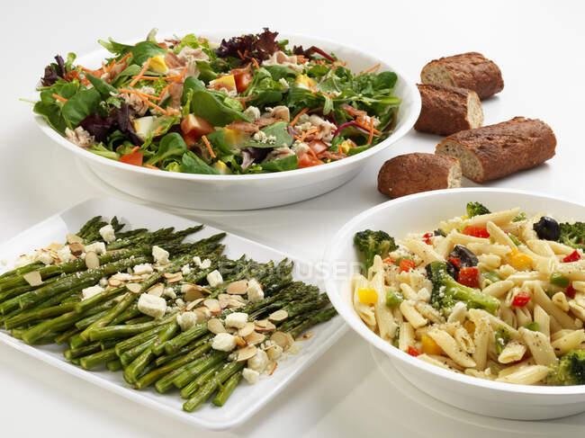 Asperges vertes, penne aux légumes et salade mixte, servies avec pain — Photo de stock