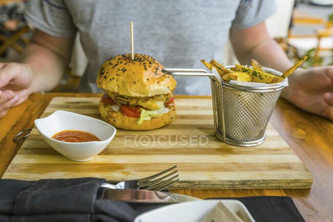 El hombre está comiendo hamburguesa y papas fritas en un restaurante - foto de stock