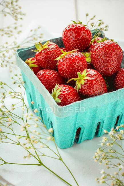 Fresas en contenedor de papel rodeado de flores silvestres - foto de stock