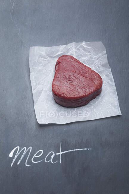 Un filete crudo de carne de res en pergamino - foto de stock