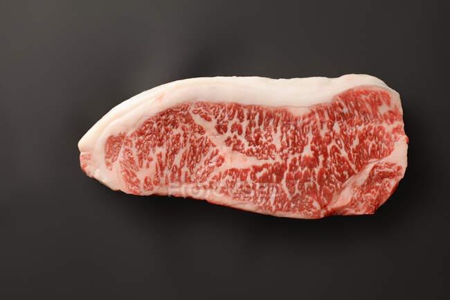 Carne de res Wagyu primer plano sobre fondo negro - foto de stock