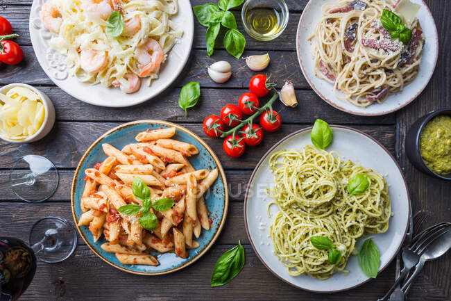 Several plates of pasta with different kinds of sauce over wooden background — Stock Photo