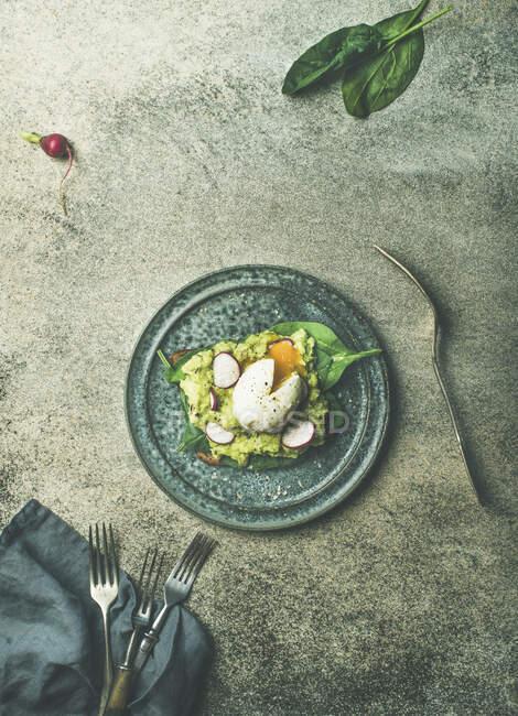 Tostadas integrales con aguacate, espinacas y huevo escalfado en plato sobre fondo de hormigón gris - foto de stock