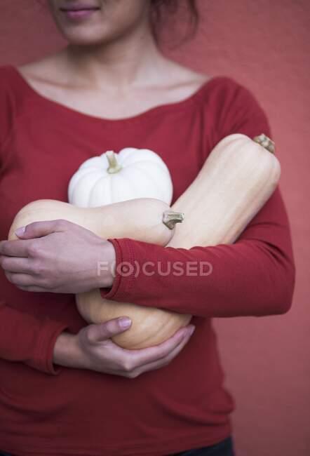 Жінка тримає різні гарбузи. — стокове фото