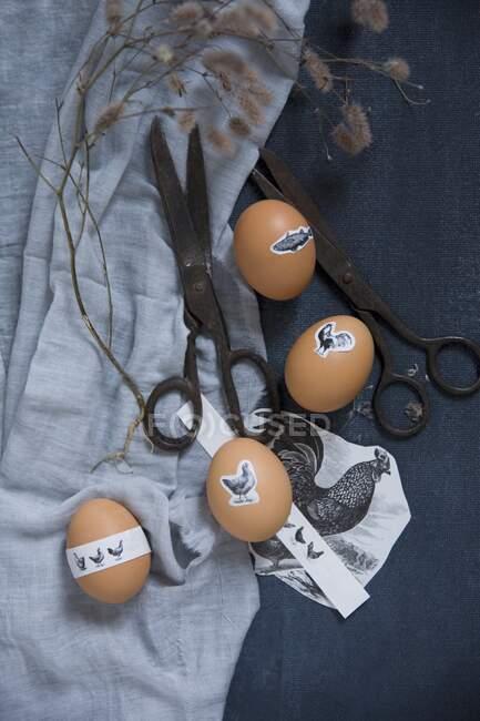 Пасхальні яйця з наклейками на тваринах на синій тканині з вінтажними ножицями. — стокове фото