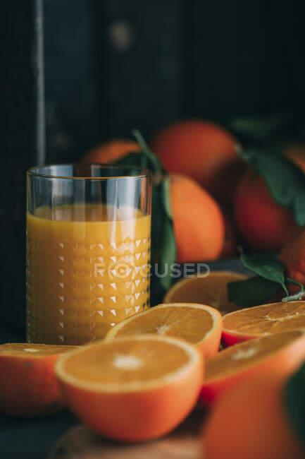 Laranjas e vidro frescos com suco de laranja — Fotografia de Stock