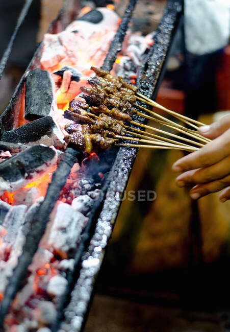 A close up of lamb satays on charcoal satay grill in Indonesia — Stock Photo