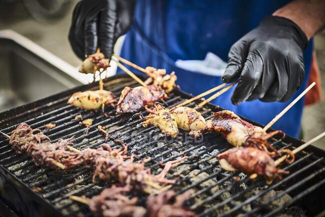 Calamari pieces on a grill in a street kitchen — Stock Photo