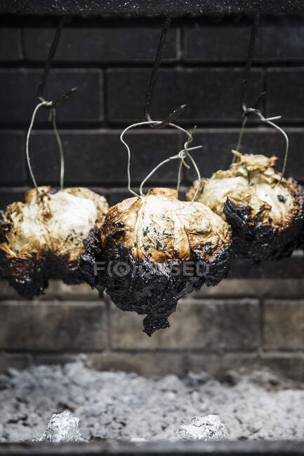 Whole cabbage cooking over fire — Stock Photo