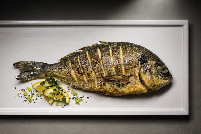 Fried sea bream on plate with lemon slice and herbs — Stock Photo