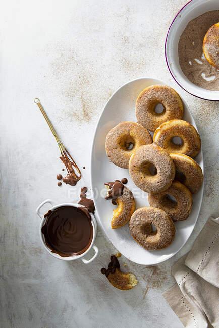 Donuts cuits au four enrobés de sucre à la cannelle et servis avec sauce au chocolat trempé — Photo de stock