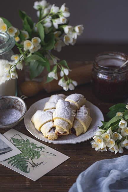 Cruasanes caseros con flores y miel sobre un fondo de madera - foto de stock