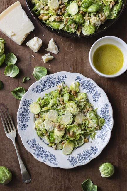 Salade de choux de brosse râpée aux noix, vinaigrette au parmesan et moutarde, parmesan, feuilles de brosse — Photo de stock