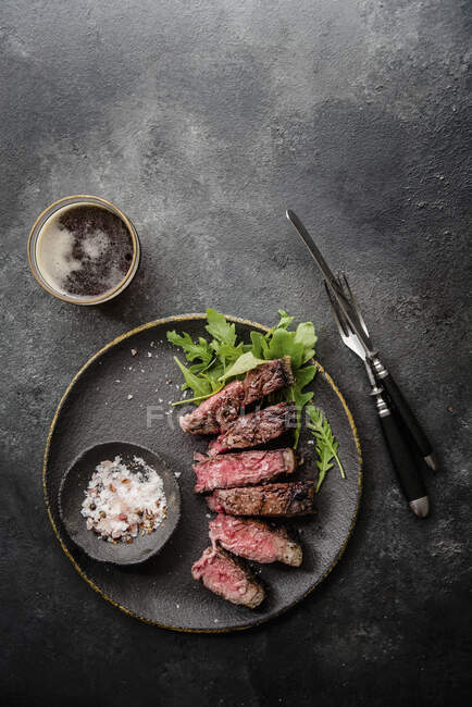 Grilled t-bone steak with rocket and spiced salt — Stock Photo