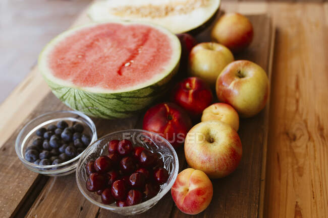 Delicious summer fruits on wooden table — Stock Photo