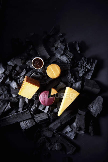 Chunks of cheese sitting on top of charcoal with a small bowl of chutney — Stock Photo