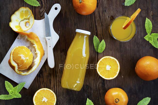 Suco de laranja em um copo e garrafa com laranjas frescas e folhas de hortelã — Fotografia de Stock