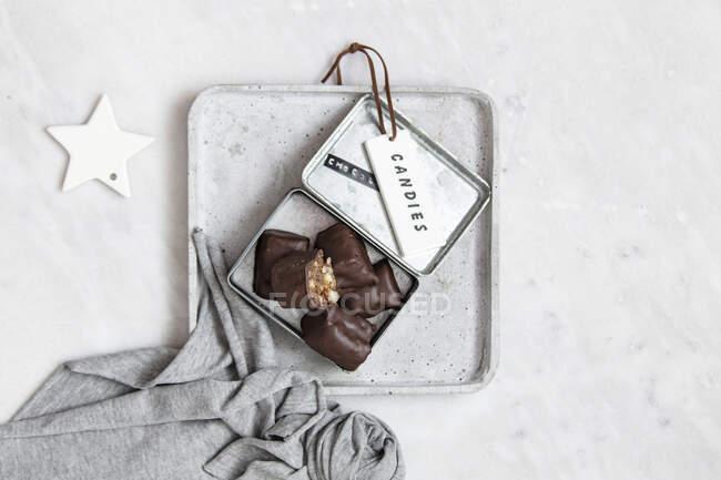 Шоколадні цукерки з горіхами і датами в подарунковій коробці на білому мармуровому тлі. — стокове фото