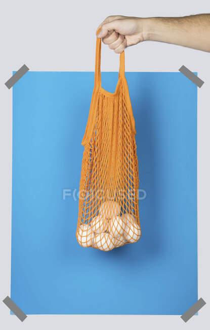 Mano que lleva el saco neto anaranjado con huevos frescos contra rectángulo azul durante la compra cero residuos - foto de stock