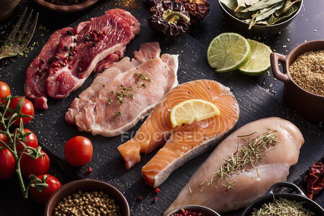 Colocación plana de proteínas rodeadas de especias y condimentos en la mesa - foto de stock
