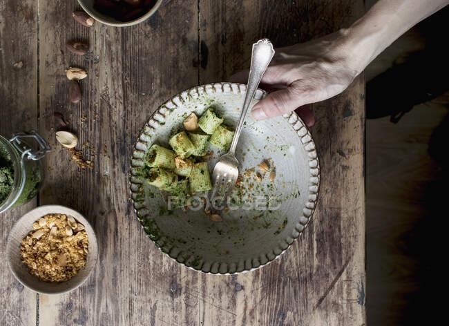 Руки тягнуть миску смачної пасти paccheri з смачним кашаловим песто та арахісом. — стокове фото