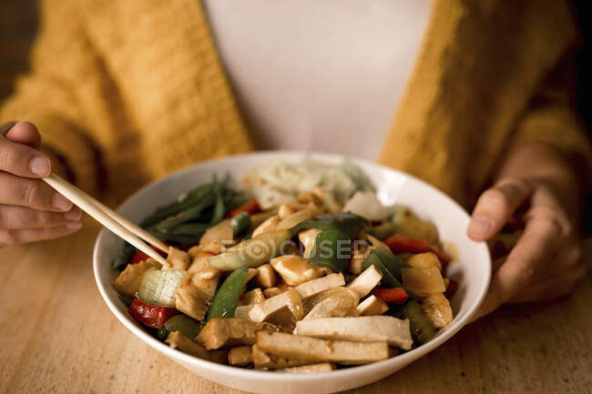 Woman eating bowl of prepared tasty vegetarian dish with healthy bell pepper, onion, carrot and mushrooms in Asian cafe — Stock Photo