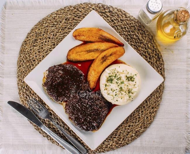 Asado Negro, Carne de vacuno, puré de papas y plátanos fritos - foto de stock