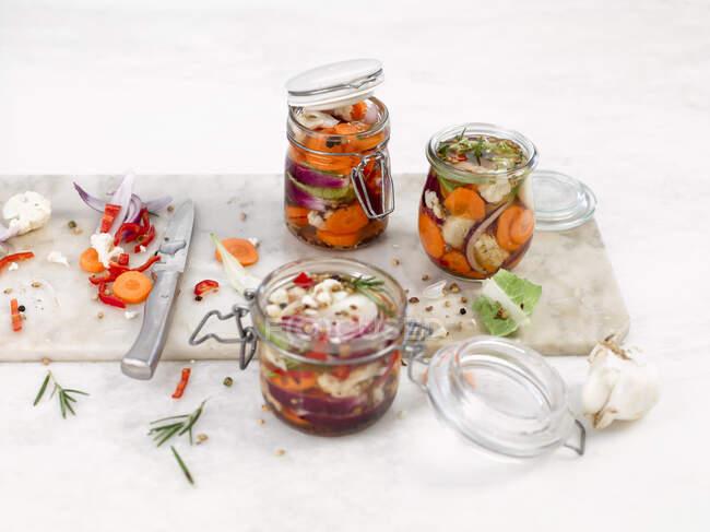 Zanahorias en escabeche y coliflor con chiles y romero - foto de stock