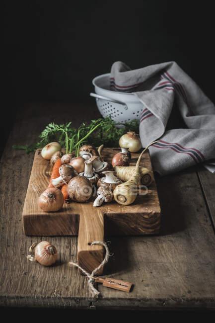 Set de sabrosas verduras frescas preparadas para cocinar en tabla de cortar de madera - foto de stock