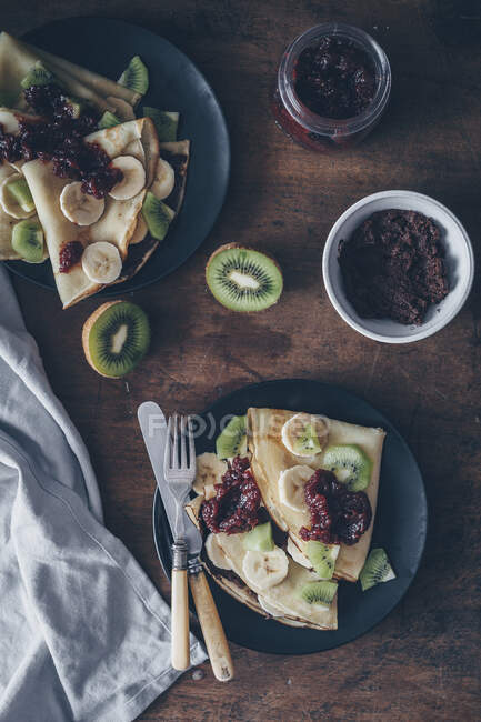 Crepes with chocolate spread, jam and fruits — Stock Photo