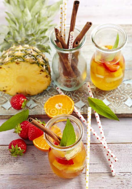 Punch de rum de abacaxi de verão com morangos, tangerinas e canela — Fotografia de Stock
