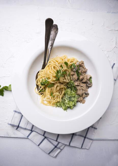 Spaghettis à la viande assaisonnée végétalienne (à base de soja texturé) et salade de concombre — Photo de stock