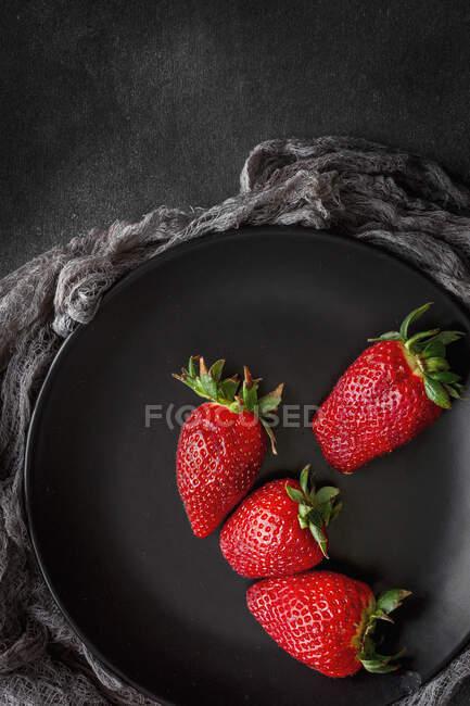 Fresas rojas y frescas planas yacen en plato negro - foto de stock