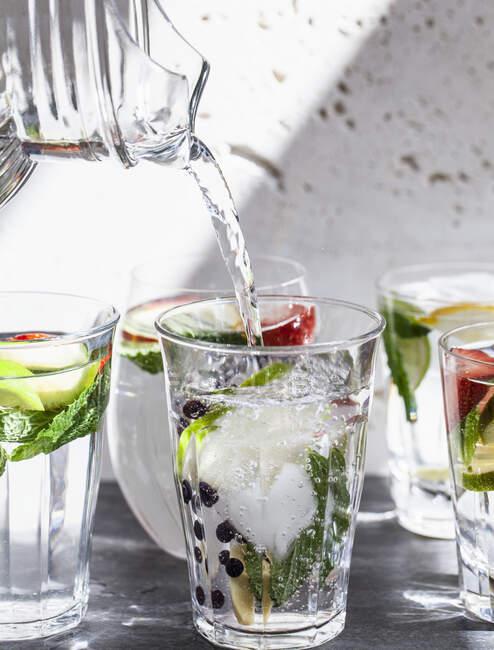 Vari bicchieri d'acqua pieni di frutta, menta e zenzero con acqua versata dalla brocca in un bicchiere — Foto stock