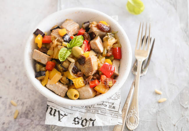 Eggplant caponata and peppers with olives raisins pine nuts and fresh swordfish - foto de stock