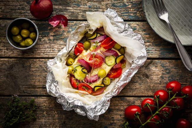 Feta con tomates, calabacín, aceitunas, cebollas y tomillo en papel pergamino - foto de stock