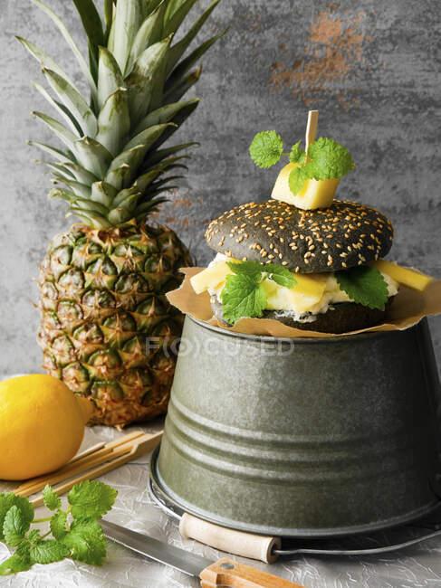 Una hamburguesa negra con quark de limón, piña y bálsamo de limón - foto de stock