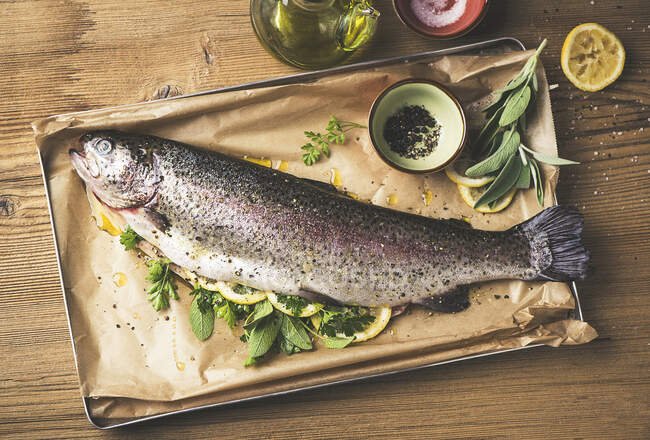 Salmon trout with herbs and lemons — Stock Photo