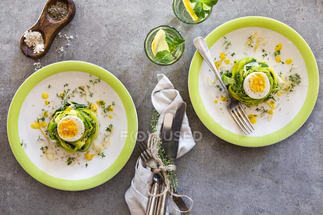 Huevos cocidos en nidos de puerro con aderezo de limón, semillas de sésamo y berro - foto de stock