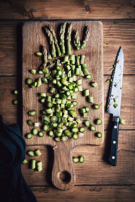 Espárragos verdes en rodajas con un cuchillo en una superficie de madera - foto de stock