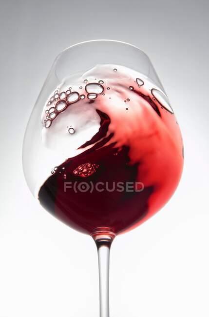 Красное вино, создающее волну в стакане — стоковое фото