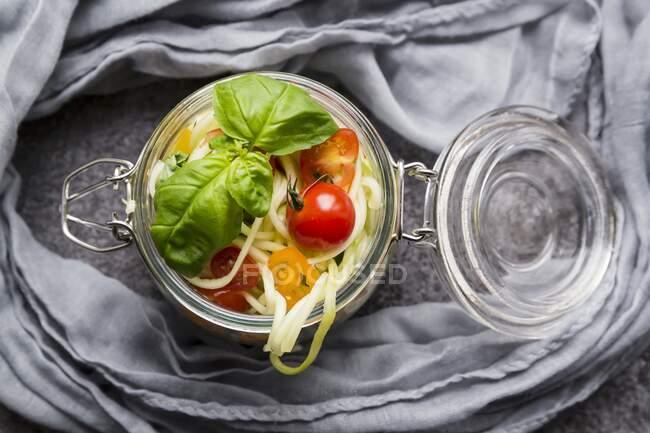 Zoodles (fideos de calabacín) en un frasco de vidrio con tomates y albahaca - foto de stock