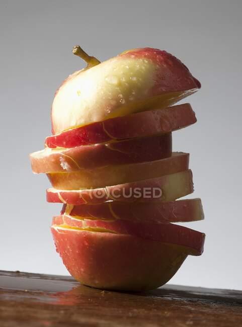 Una manzana cortada en rodajas, con gotas de agua - foto de stock