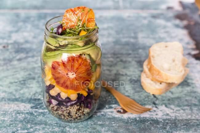 Ensalada de quinua en un frasco de vidrio con col roja, garbanzos, aguacate, naranja sangre y berro - foto de stock