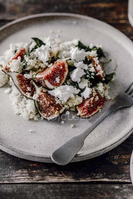 Салат з просо, котеджний сир, шпинат і інжир. — стокове фото