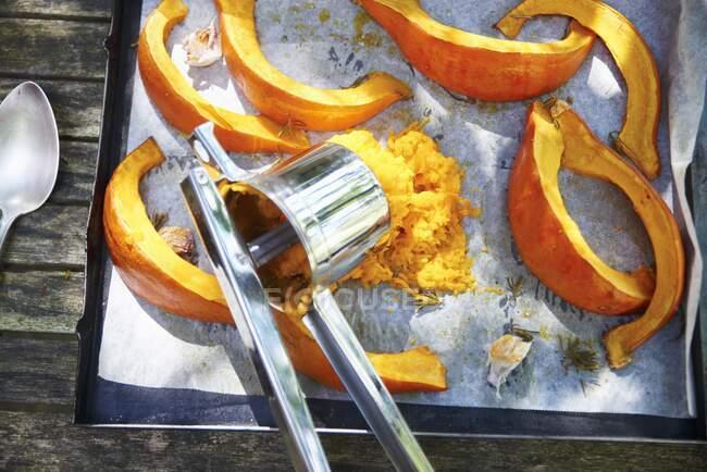 Im Ofen gebratener Kürbis, teilweise püriert, auf einem Backblech — Stockfoto