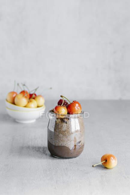 Скляна банка з шоколадним пудингом складалася з йогурту та насіння чіа і прикрашена білою вишнею. — стокове фото