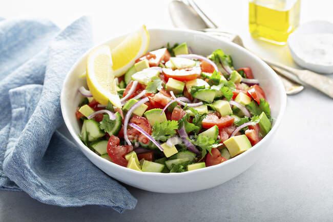 Свіжі овочі нарізали салат помідорами, огірком і авокадо. — стокове фото