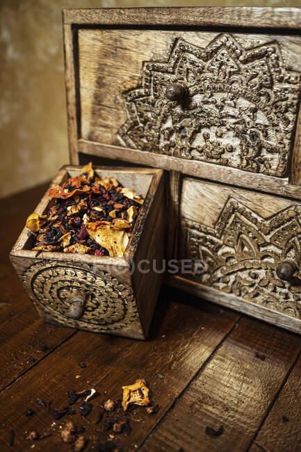 Alto ángulo de viejo cajón envejecido con pétalos de flores secas y hierbas colocadas en la mesa - foto de stock